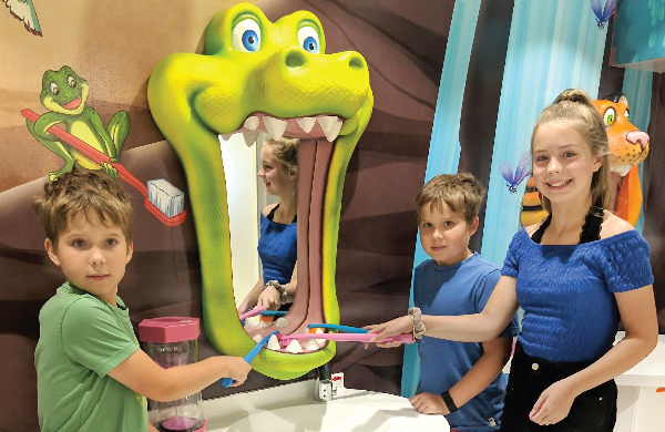 kids smiling in a dental office with tooth brushes, alligator brushing mirror, and jungle wall mural