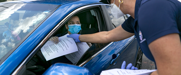 Medical patient waits in car and does paperwork.